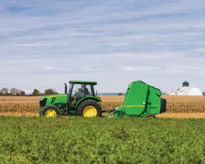 The 440E Round Baler by John Deere for sale at C&B Operations, working in a field with a row-crop tractor.